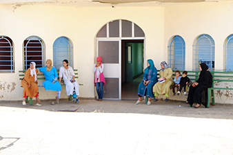 Several women and children are waiting outside Moroccan medical clinic