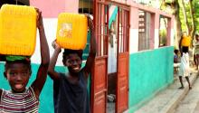Children in Haiti are Carrying Yellow Water Jugs and Smiling at Camera